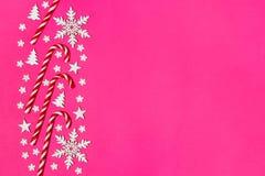 Ο κάλαμος καραμελών Χριστουγέννων είπε ψέματα ομοιόμορφα στη σειρά στο ρόδινο υπόβαθρο με διακοσμητικά snowflake και το αστέρι Επ Στοκ εικόνες με δικαίωμα ελεύθερης χρήσης