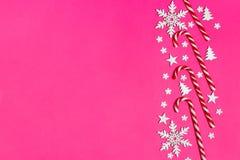 Ο κάλαμος καραμελών Χριστουγέννων είπε ψέματα ομοιόμορφα στη σειρά στο ρόδινο υπόβαθρο με διακοσμητικά snowflake και το αστέρι Επ Στοκ φωτογραφία με δικαίωμα ελεύθερης χρήσης