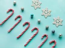 Ο κάλαμος καραμελών Χριστουγέννων είπε ψέματα ομοιόμορφα στη σειρά στο μπλε υπόβαθρο επίπεδος Στοκ Εικόνες