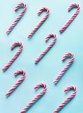 Ο κάλαμος καραμελών Χριστουγέννων είπε ψέματα ομοιόμορφα στη σειρά στο μπλε Επίπεδος βάλτε και τοπ άποψη Στοκ Εικόνες