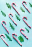 Ο κάλαμος καραμελών Χριστουγέννων είπε ψέματα ομοιόμορφα στη σειρά στο μπλε Επίπεδος βάλτε και τοπ άποψη Στοκ φωτογραφίες με δικαίωμα ελεύθερης χρήσης