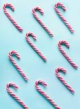 Ο κάλαμος καραμελών Χριστουγέννων είπε ψέματα ομοιόμορφα στη σειρά στο μπλε υπόβαθρο Επίπεδος βάλτε και τοπ άποψη πρότυπο Στοκ Εικόνες