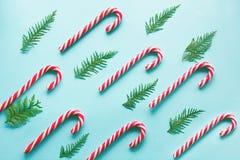 Ο κάλαμος καραμελών Χριστουγέννων είπε ψέματα ομοιόμορφα στη σειρά στο μπλε υπόβαθρο Επίπεδος βάλτε Στοκ Εικόνα