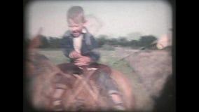 Ο κάουμποϋ περπατά το μικρό παιδί στο άλογο - τρύγος 8mm απόθεμα βίντεο