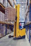 Ο κίτρινος για τους πεζούς στοιβαχτής ανυψώνει την παλέτα με τα κιβώτια στα ράφια Στοκ Εικόνες