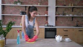 Ο καθαρισμός σπιτιών, όμορφη γυναίκα οικονόμων στα λαστιχένια γάντια για τον καθαρισμό τρίβει τα σκονισμένα έπιπλα με το απορρυπα απόθεμα βίντεο