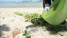 Ο καθαριστής που συλλέγει τα απορρίματα στην αμμώδη παραλία στην πράσινη πλαστική τσάντα, πλαστικά μπουκάλια συλλέγεται στην παρα απόθεμα βίντεο