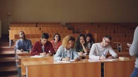 Ο καθηγητής διαβάζει τη διάλεξη στην ομάδα πολυφυλετικών σπουδαστών που στέκονται στην τάξη με τα έγγραφα και που μιλούν ενώ νεολ απόθεμα βίντεο