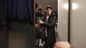 Ο καθιερώνων τη μόδα τύπος υπολογίζει την εικόνα του με τη μεγάλο τσάντα, το παλτό και την ΚΑΠ στον καθρέφτη του καταστήματος φιλμ μικρού μήκους