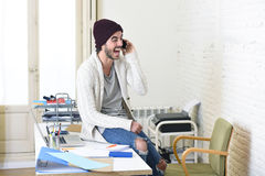 Ο καθιερώνων τη μόδα επιχειρηματίας στο beanie και δροσερός hipster άτυπος φαίνονται ομιλία ευτυχής στο κινητό τηλέφωνο Στοκ Φωτογραφία