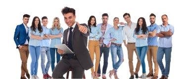 Ο καθισμένος αρχηγός ομάδας επιχειρηματιών με την ταμπλέτα κάνει το εντάξει σημάδι στοκ φωτογραφία