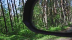 Ο καθρέφτης του αυτοκινήτου απεικονίζει τους δασικούς γύρους ένα αυτοκίνητο μέσω των ξύλων φιλμ μικρού μήκους