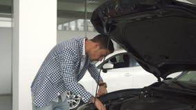Ο καινούργιος ιδιοκτήτης του αυτοκινήτου μελετά τις λεπτομέρειες σε μια ανοικτή κουκούλα στοκ εικόνες
