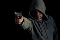 Ο κακοποιός στο hoodie δείχνει το πυροβόλο όπλο Στοκ φωτογραφία με δικαίωμα ελεύθερης χρήσης