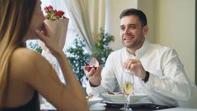 Ο καλά ντυμένος όμορφος τύπος κάνει μια πρόταση στη νέα κυρία δειπνώντας στο εστιατόριο Μιλά έπειτα να δώσει την απόθεμα βίντεο