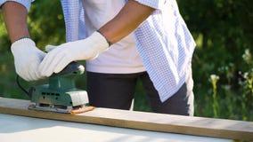 Ο καλλιεργημένος πυροβολισμός του ατόμου βάζει στα γάντια και στρώνει με άμμο την ξύλινη σανίδα με την ηλεκτρική μηχανή απόθεμα βίντεο