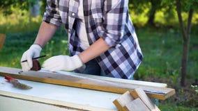 Ο καλλιεργημένος πυροβολισμός του θηλυκού ξυλουργού μετρά την ξύλινη σανίδα με τη μέτρηση της ταινίας φιλμ μικρού μήκους