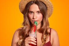 Ο καλλιεργημένος στενός επάνω πυροβολισμός σοβαρός ευχάριστος να φανεί θηλυκός κρατά το κρύο φρέσκο ποτό, ποτό με το άχυρο, έχει  στοκ εικόνες με δικαίωμα ελεύθερης χρήσης