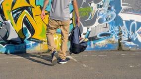 Ο καλλιτέχνης έρχεται μέχρι τον τοίχο που καλύπτεται με τα γκράφιτι και ρίχνει ένα σύνολο τσαντών των χρωμάτων ψεκασμού στο έδαφο φιλμ μικρού μήκους