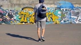 Ο καλλιτέχνης γκράφιτι ανυψώνει το σακίδιο πλάτης του με τα μεταλλικά κουτιά χρωμάτων και πηγαίνει προς τον τοίχο γκράφιτι φιλμ μικρού μήκους