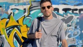 Ο καλλιτέχνης γκράφιτι εγκαταλείπει έναν τοίχο γκράφιτι με ένα σακίδιο πλάτης στους ώμους του απόθεμα βίντεο