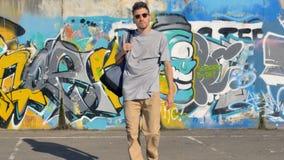 Ο καλλιτέχνης γκράφιτι με μια τσάντα στον ώμο του πηγαίνει μακρυά από τον τοίχο που καλύπτεται με τις εικόνες γκράφιτι απόθεμα βίντεο