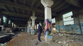 Ο καλλιτέχνης γκράφιτι στην προστατευτική μάσκα χρωματίζει στην υψηλή στήλη στο εγκαταλειμμένο βιομηχανικό κτήριο Δημιουργικοί άν απόθεμα βίντεο