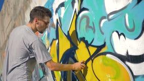Ο καλλιτέχνης γκράφιτι χρωματίζει ένα μαύρο τρίγωνο στην κίτρινη επιστολή, σωστή άποψη απόθεμα βίντεο