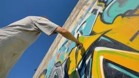 Ο καλλιτέχνης γκράφιτι χρωματίζει μια κίτρινη επιστολή στον τοίχο, άποψη από κάτω από απόθεμα βίντεο