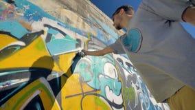Ο καλλιτέχνης γκράφιτι χρωματίζει μια κίτρινη επιστολή στον τοίχο, άποψη από τη αριστερή πλευρά, από κάτω από φιλμ μικρού μήκους