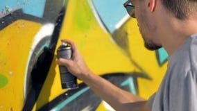 Ο καλλιτέχνης γκράφιτι χρωματίζει μια μαύρη γραμμή κοντά στην κίτρινη επιστολή στον τοίχο απόθεμα βίντεο