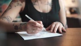 Ο καλλιτέχνης δερματοστιξιών κάνει ένα σκίτσο της δερματοστιξίας σε χαρτί σε ένα εγχώριο στούντιο φιλμ μικρού μήκους