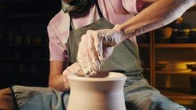 Ο καλλιτέχνης ενεργοποιεί τα χέρια, τα οποία δημιουργώντας ήπια σωστά διαμορφωμένο χειροποίητο από τον άργιλο Παραδοσιακή αγγειοπ απόθεμα βίντεο
