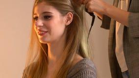 Ο καλλιτέχνης και ο κομμωτής Makeup προετοιμάζουν τη νύφη πριν από το γάμο Ο κομμωτής-στιλίστας με το σύντομο μοντέρνο hairstyle  απόθεμα βίντεο