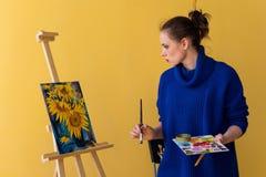 Ο καλλιτέχνης κοριτσιών χρωματίζει τους ηλίανθους Στοκ εικόνα με δικαίωμα ελεύθερης χρήσης