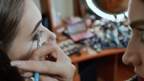 Ο καλλιτέχνης κοριτσιών makeup χρωματίζει τα μάτια του προτύπου κοριτσιών Χρωματισμός των γωνιών των ματιών απόθεμα βίντεο
