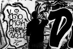 Ο καλλιτέχνης οδών ολοκληρώνει μια εργασία για έναν τοίχο με τους ψεκασμούς κατά τη διάρκεια ενός ανταγωνισμού στοκ εικόνα με δικαίωμα ελεύθερης χρήσης