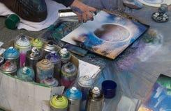 Ο καλλιτέχνης οδών χρωματίζει μια εικόνα με ένα αερόλυμα Στοκ φωτογραφίες με δικαίωμα ελεύθερης χρήσης