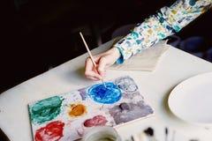 Ο καλλιτέχνης που εργάζεται σε μια παλέτα των χρωμάτων Λήψη μιας βούρτσας, η διαδικασία του σχεδίου Στοκ φωτογραφία με δικαίωμα ελεύθερης χρήσης