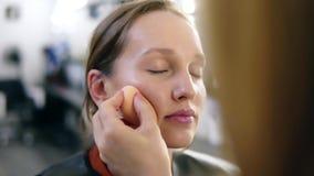 Ο καλλιτέχνης σύνθεσης βάζει τα περιγράμματα στα ζυγωματικά του κοριτσιού Επαγγελματικό Makeup Νέο, ξανθό πρότυπο απόθεμα βίντεο