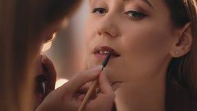 Ο καλλιτέχνης σύνθεσης εφαρμόζει το κόκκινο κραγιόν με μια επαγγελματική βούρτσα στο πρόσωπο ενός καυκάσιου ξανθού προτύπου Κινημ απόθεμα βίντεο
