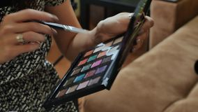 Ο καλλιτέχνης σύνθεσης κρατά mascara στα μάτια της Κινηματογράφηση σε πρώτο πλάνο μιας επαγγελματικής εξάρτησης makeup απόθεμα βίντεο