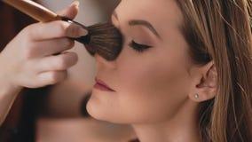 Ο καλλιτέχνης σύνθεσης τελειώνει makeup με την εφαρμογή της σκόνης με μια επαγγελματική βούρτσα στο πρόσωπο ενός καυκάσιου ξανθού απόθεμα βίντεο
