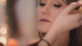 Ο καλλιτέχνης σύνθεσης τελειώνει makeup με την εφαρμογή της σκόνης με μια επαγγελματική βούρτσα στο πρόσωπο ενός καυκάσιου ξανθού φιλμ μικρού μήκους