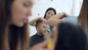 Ο καλλιτέχνης σύνθεσης χρωματίζει eyelashes του νέου θηλυκού και το άτομο στον κουρέα κοιτάζει από την πλευρά απόθεμα βίντεο