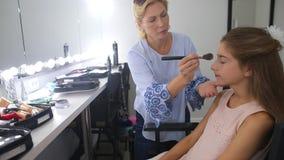 Ο καλλιτέχνης σύνθεσης makeup σε ένα κορίτσι φιλμ μικρού μήκους