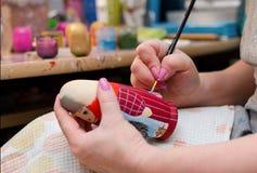 Ο καλλιτέχνης σύρει ένα κούκλα-matryoshka Κινηματογράφηση σε πρώτο πλάνο χεριών στοκ εικόνα με δικαίωμα ελεύθερης χρήσης