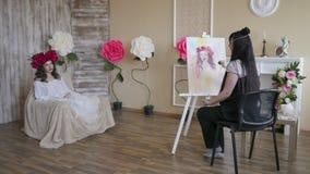 Ο καλλιτέχνης σύρει ένα πορτρέτο από τη φύση Όμορφο πρότυπο, με ένα στεφάνι των ερυθρών peonies σε επικεφαλής του, που θέτει τη σ στοκ εικόνες