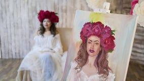 Ο καλλιτέχνης σύρει ένα πορτρέτο από τη φύση Όμορφο πρότυπο, με ένα στεφάνι των ερυθρών peonies σε επικεφαλής του, που θέτει τη σ στοκ φωτογραφίες με δικαίωμα ελεύθερης χρήσης