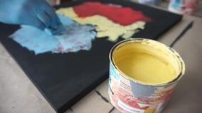 Ο καλλιτέχνης χρωματίζει μια αφηρημένη εικόνα με ένα σφουγγάρι Το Α μπορεί κίτρινου να χρωματίσει Φορημένα γάντια χέρια Στούντιο  απόθεμα βίντεο